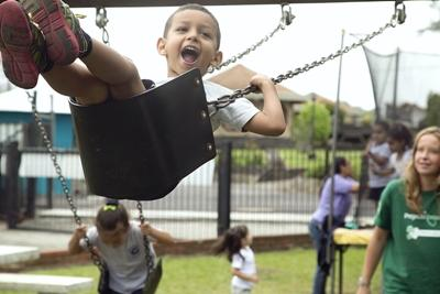 Volunteer pushing a child on a swing at a care placement in Costa Rica