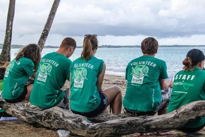Projects Abroad Shark Conservation volunteers resting in the shade of coconut trees during a beach clean-up community day – one of our many gap year ideas.