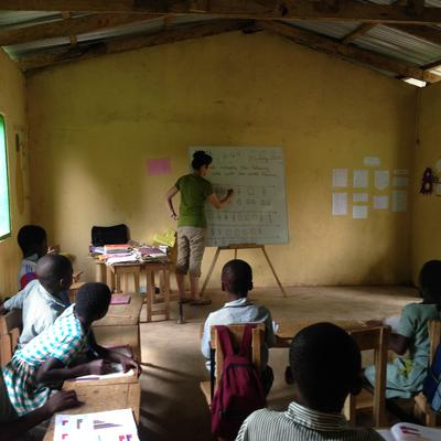 Teaching volunteer in Ghana writing on a blackboard