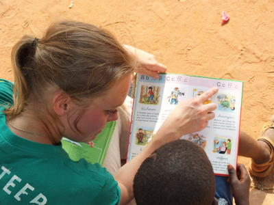 A volunteer travelling to Africa practices reading aloud with a child
