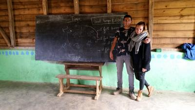 Male and female Projects Abroad volunteers pose in front of a chalkboard in Madgascar