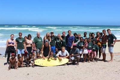 Group of Projects Abroad volunteers and children volunteering in summer at a surfing project in South Africa