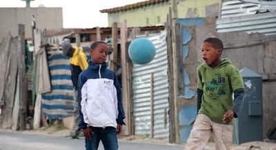 Boys play soccer on street in South Africa