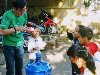 Children in Vietnam practice brushing their teeth while volunteer demonstrates