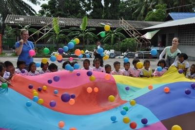 Volunteers playing with children at care project Thailand