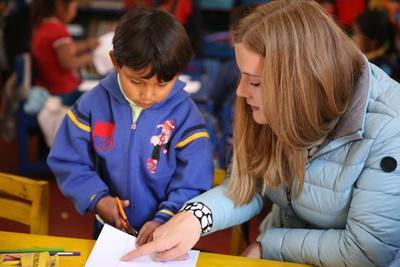Projects Abroad Care volunteer explains to young child how to cut using scissors