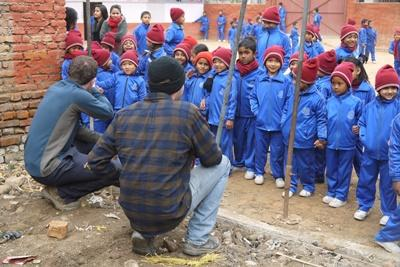Projects Abroad male volunteers meet school children at their new building on the Disaster Relief project in Nepal