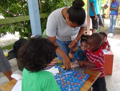 Care volunteer plays with children in Belize