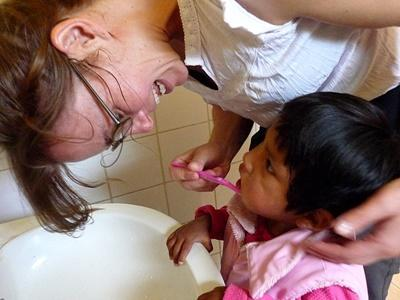 Volunteer helps a child brush their teeth