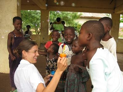 Volunteer lets children blow bubbles at Care project, Ghana
