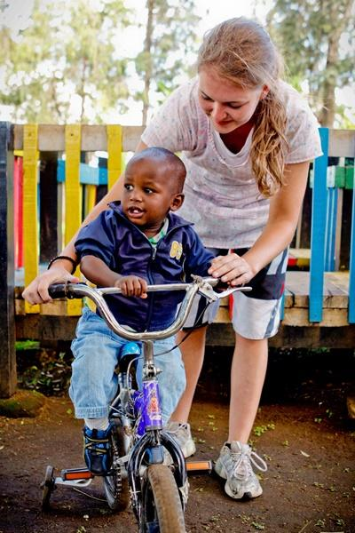 A female volunteer helps a child ride his bicycle in Kenya.