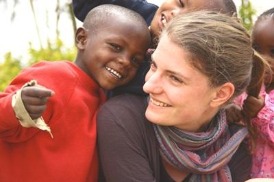 A child smiles with a female volunteer in Kenya.