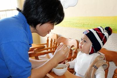 A volunteer feeds a young child at Care placement in Mexico