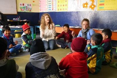 Two female Projects Abroad volunteers play educational games in a group in a class in Patan, Nepal