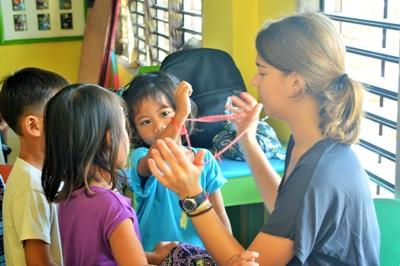 A Care volunteer plays with the children in the Philippines