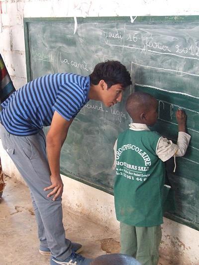 Care volunteer helps child at kindergarten learn to write