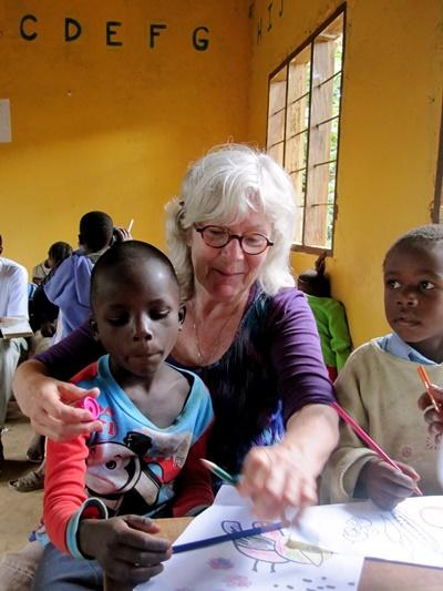 Volunteer helps children at a Care placement with colouring pictures