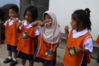 A volunteer helps children at Care placement to clean their teeth