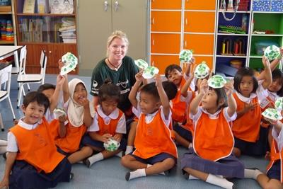 A Projects Abroad volunteer with young children during a Care project in Thailand, Asia
