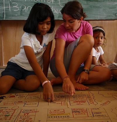 A Care volunteer plays a game with children in Thailand