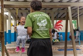 A child and volunteer interact on a swing set