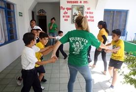 A volunteer plays with children on a Care Project placement