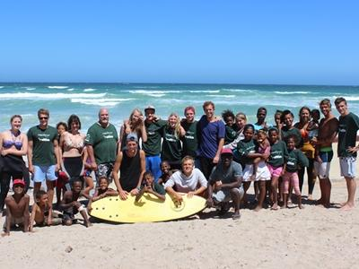 Projects Abroad volunteers and South African children have fun at the beach in Muizenberg, Cape Town.