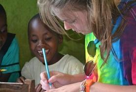 A child watches a volunteer on a placement in Ghana