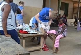 A Medicine volunteer in Ghana assists with cleaning a child's wound during a healthcare outreach over the Christmas period.