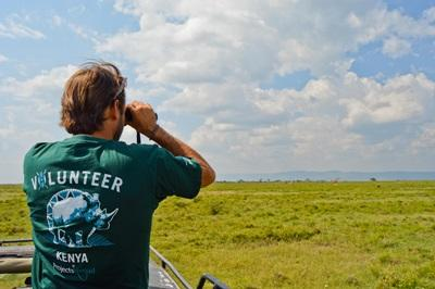 A Projects Abroad Conservation volunteer from France looks at a giraffe through binoculars at the Soysambu conservancy in Kenya
