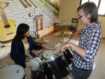 A local girl learns to play a musical instrument with the help of a volunteer in Bolivia