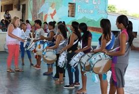 A volunteer leads a trope of drummers during a musical showcase