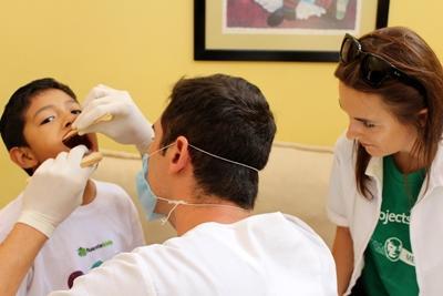 Denistry volunteer checks child's teeth in Mexico