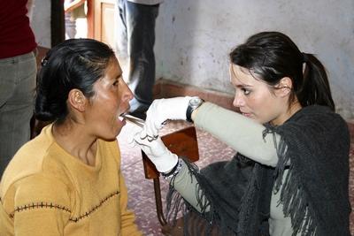 Volunteer checks patient's teeth in Peru