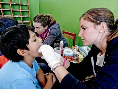 Volunteer on an Elective placement examines a child in Peru