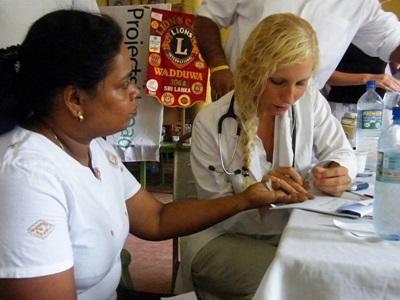 Medical Elective volunteer examines a patient's hand in Peru