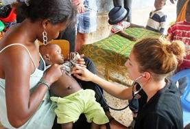 Two Medicine Elective interns assist a local doctor in Togo with administering HIV tests during a medical outreach.