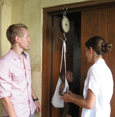 Elective volunteers weigh a baby in Ghana