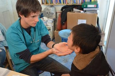 Nursing volunteer examines a child's mouth in Mongolia