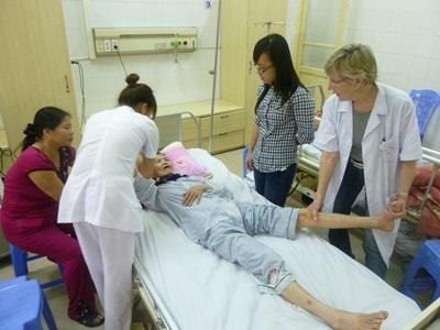 Volunteers examine an elderly patient in Vietnam