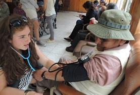 A Nursing Elective intern works closely with a disabled child at her volunteer placement in Bolivia.