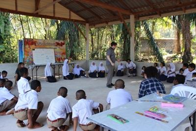 A male volunteer teaching English in Thailand, Asia