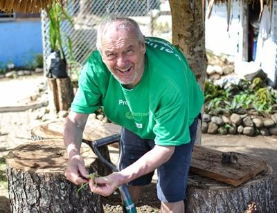 An older Projects Abroad volunteer works in a Fiji village greenhouse garden outside of Nadi
