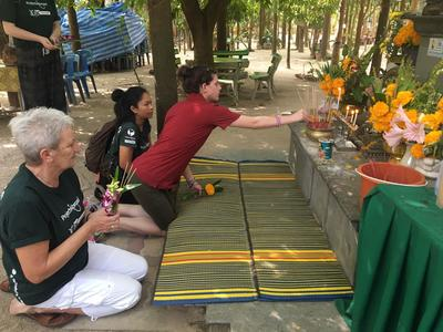 An older Projects Abroad volunteer waits to make an offering during a temple day in Thailand