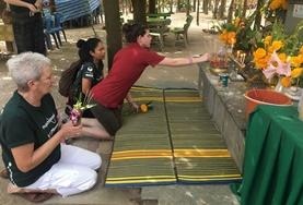 An older volunteer makes an offering at a temple during her free time while Teaching in Thailand.
