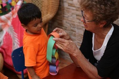 An older volunteer teaches arts and crafts to a young boy.