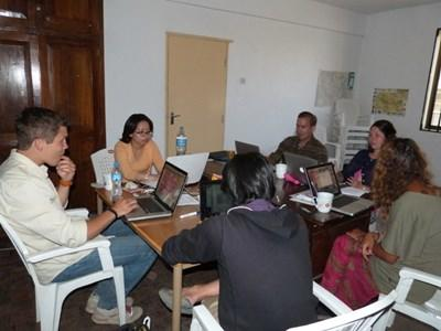 Volunteers hold a meeting at their Journalism project