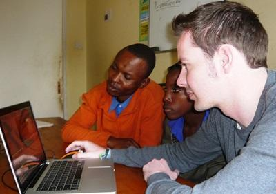 Journalism volunteer in Tanzania shows staff his work