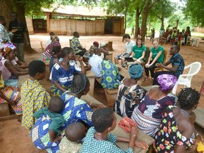 Journalism volunteers talk to a group of Togolese people