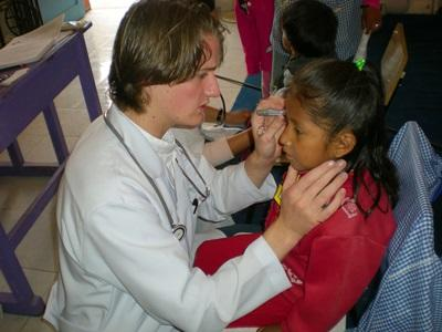 Medical project volunteer checking a girl in Bolivia, South America